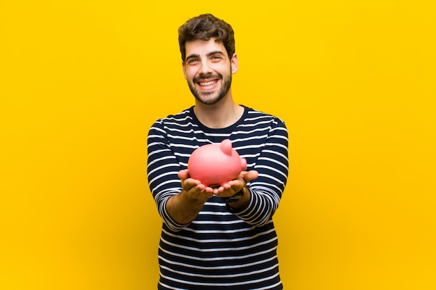 Young handsome man holding a piggy bank on orange Premium Photo