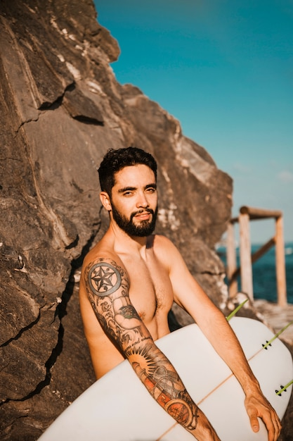 Young handsome man holding surf board near stones Free Photo