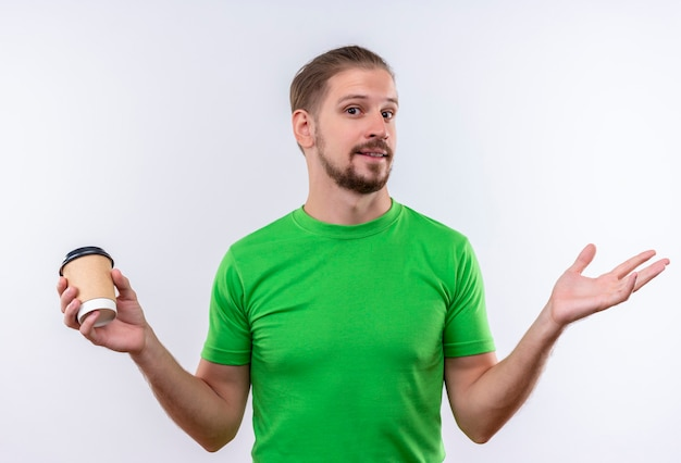 白い背景の上に立って笑って手を広げてカメラを見てコーヒーカップを保持している緑のtシャツの若いハンサムな男 無料写真