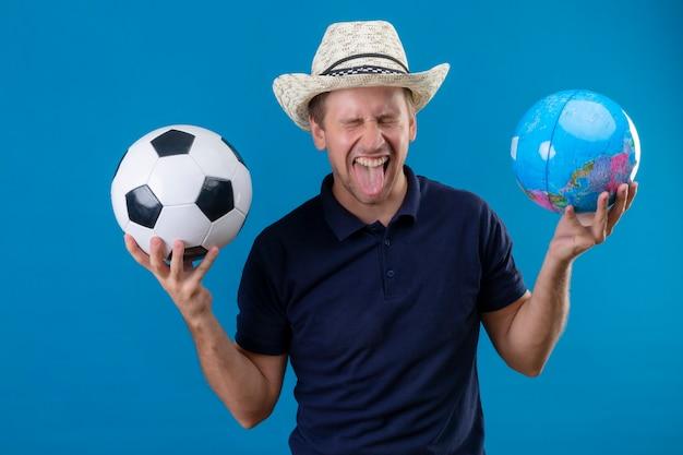 Молодой красавец в летней шляпе, держащий футбольный мяч и глобус, сумасшедший счастливый крик в увлечении, высунув язык, стоя на синем фоне Бесплатные Фотографии
