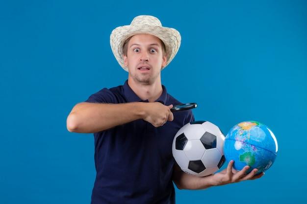 Молодой красавец в летней шляпе, держащий футбольный мяч и глобус, собирается смотреть на глобус через увеличительное стекло, выглядит удивленным и пораженным, стоя на синем фоне Бесплатные Фотографии