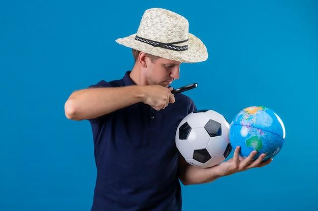 Молодой красавец в летней шляпе держит футбольный мяч и глобус, глядя на них через увеличительное стекло, заинтригованный, стоя на синем фоне Бесплатные Фотографии