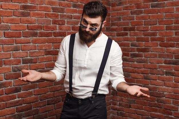 レンガの壁でポーズを身振りで示すサングラスで若いハンサムな男。 無料写真