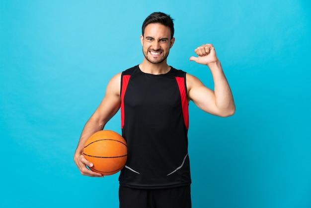 バスケットボールをしている青い背景に孤立し、彼自身を誇りに思っている若いハンサムな男 Premium写真