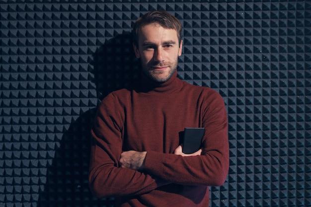 Молодой, красивый мужчина, прислонившись к серой стене со скрещенными руками. улыбающийся мужчина, глядя на камеру, держа телефон. игра света и тень Premium Фотографии