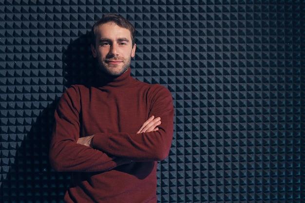 Молодой, красивый мужчина, прислонившись к серой стене со скрещенными руками. улыбающийся мужчина, глядя на камеру. Premium Фотографии