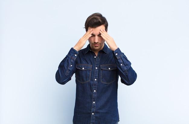 ストレスと欲求不満を探している若いハンサムな男、頭痛で圧力の下で働いて、青い壁に対する問題で悩んで Premium写真