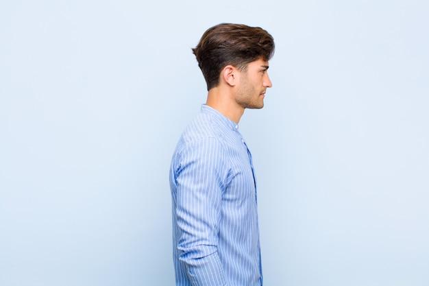 前方のスペースをコピーしようと考えて、考えて、想像して、または青い背景に空想のプロファイルビューで若いハンサムな男 Premium写真