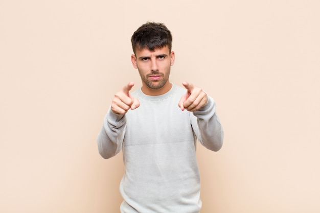 Young handsome man pointing forward with both fingers and angry expression, telling you to do your duty against warm wall Premium Photo