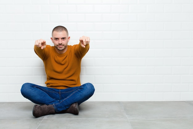 Young handsome man pointing forward with both fingers and angry expression, telling you to do your duty sitting on the floor Premium Photo