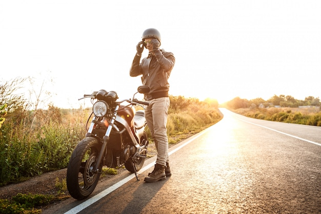 Young handsome man posing near his motorbike at countryside road. Free Photo