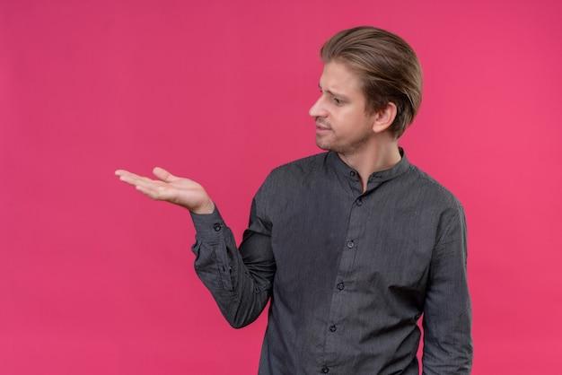 ピンクの壁の上に立っている彼の手の腕でコピースペースを提示する若いハンサムな男 無料写真