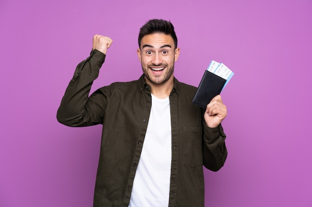 Young handsome man over purple happy in vacation with passport and plane tickets Premium Photo