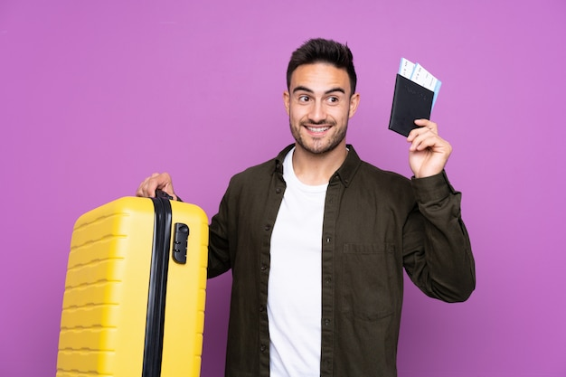 Young handsome man over purple in vacation with suitcase and passport Premium Photo