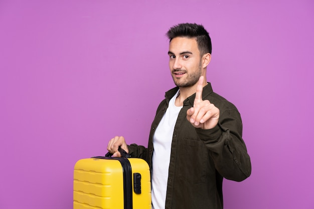 Young handsome man over purple in vacation with travel suitcase and counting one Premium Photo