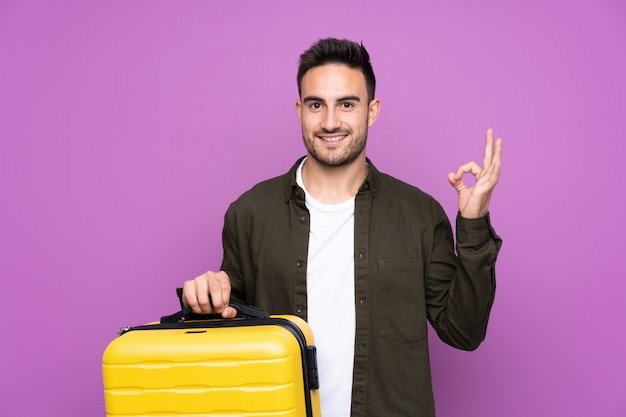 Young handsome man over purple in vacation with travel suitcase and a hat Premium Photo