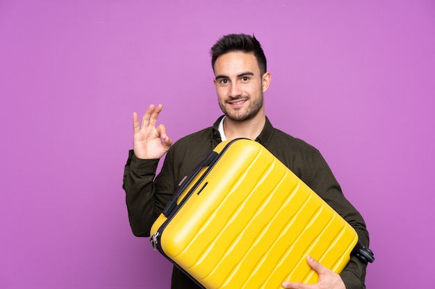 Young handsome man over purple in vacation with travel suitcase and making ok sign Premium Photo