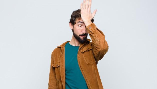 愚かな間違いをしたり、覚えたりした後、額に思考の手のひらを上げる若いハンサムな男、または覚えて、平らな壁に馬鹿げた感じ Premium写真
