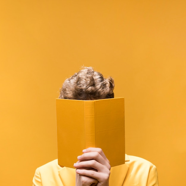 Young handsome man reading a book in a yellow scene Free Photo