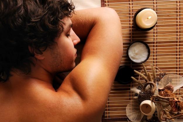 Il rilassamento e la ricreazione dell'uomo bello giovane sul salone della stazione termale. veduta dall'alto Foto Gratuite