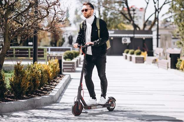 Young handsome man riding on scooter in the park Free Photo