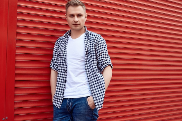 Young handsome man in a shirt and jeans near the red gate Premium Photo