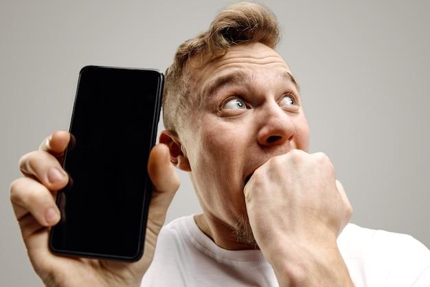 Giovane uomo bello che mostra lo schermo dello smartphone su sfondo grigio con una faccia a sorpresa. emozioni umane, concetto di espressione facciale Foto Gratuite