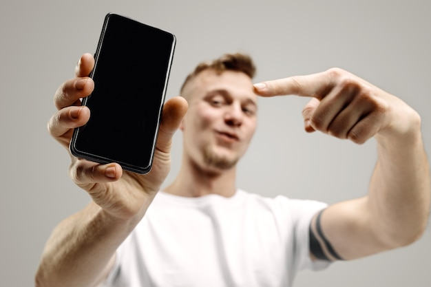 Young handsome man showing smartphone screen over gray space with a surprise face Free Photo