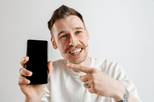 Молодой красавец показывает экран смартфона над серым пространством с удивленным лицом Бесплатные Фотографии