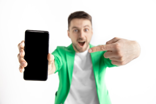 Young handsome man showing smartphone screen and signing ok isolated on gray walll Free Photo