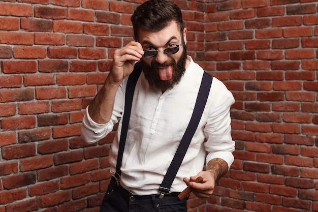 Young handsome man showing tongue holding cigar on brick wall. Free Photo
