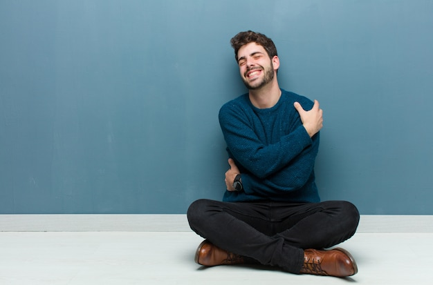 Young handsome man sitting on floor feeling in love, smiling, cuddling and hugging self, staying single, being selfish and egocentric Premium Photo