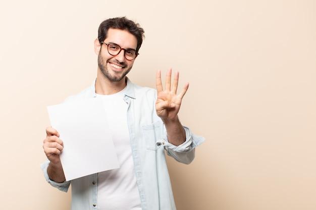Молодой красивый мужчина улыбается и выглядит дружелюбно, показывает номер четыре или четвертый с рукой вперед, отсчитывая Premium Фотографии