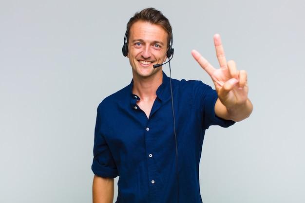 笑顔で幸せそうに見える若いハンサムな男、のんきで前向きで、片手で勝利または平和を身振りで示す Premium写真