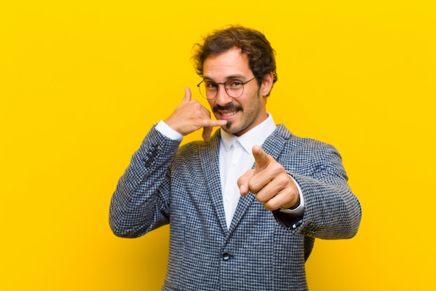 Young handsome man smiling cheerfully and pointing to camera while making a call you later gesture, talking on phone against orange wall Premium Photo