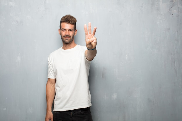 Young handsome man smiling and looking satisfied and happy, counting number three with fingers. Premium Photo