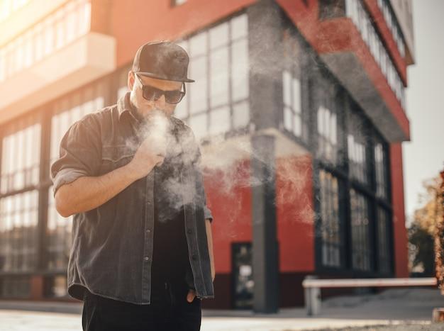 都市の場所でアークで煙る若いハンサムな男 Premium写真