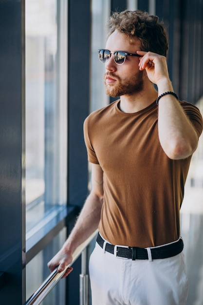 Young handsome man standing by the window at the airport Free Photo
