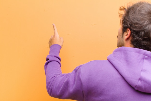 Young handsome man standing and pointing to object on copy space, rear view against orange wall Premium Photo