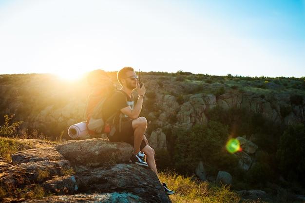 Young handsome man talking on walkie talkie radio, enjoying canyon view Free Photo