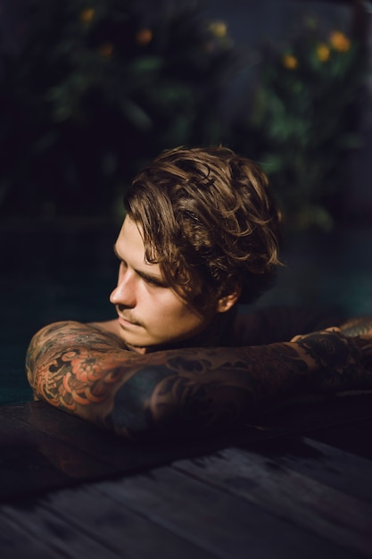 Young handsome man in tattoos resting in the outdoor pool. Free Photo