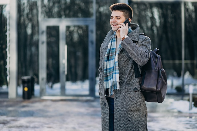 Young handsome man traveller using phone outside Free Photo