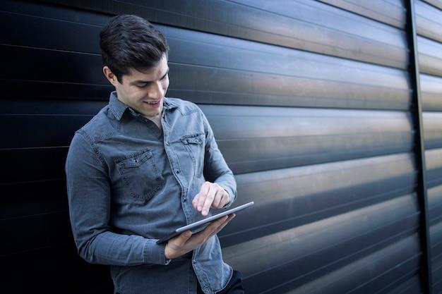 Giovane uomo bello che digita sul suo tablet pc Foto Gratuite