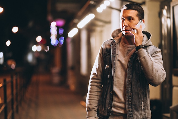 Young handsome man using phone at night in the street Free Photo