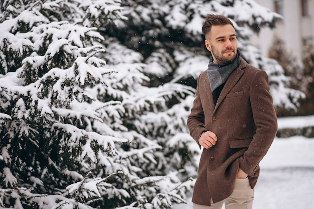 Young handsome man walking in a winter forest Free Photo