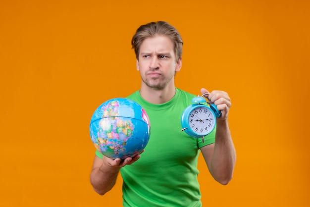Молодой красавец в зеленой футболке держит глобус и будильник, недовольно смотрит в сторону с нахмуренным лицом, стоя над оранжевой стеной Бесплатные Фотографии