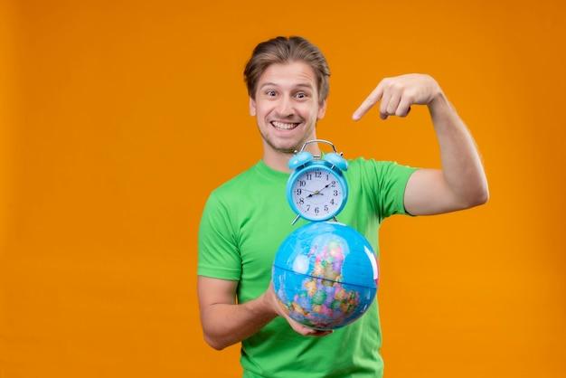Молодой красавец в зеленой футболке держит глобус и будильник, указывая пальцем на него, весело улыбаясь, стоя над оранжевой стеной Бесплатные Фотографии
