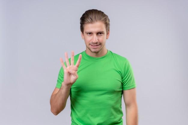 Молодой красавец в зеленой футболке показывает и показывает пальцами номер три Бесплатные Фотографии