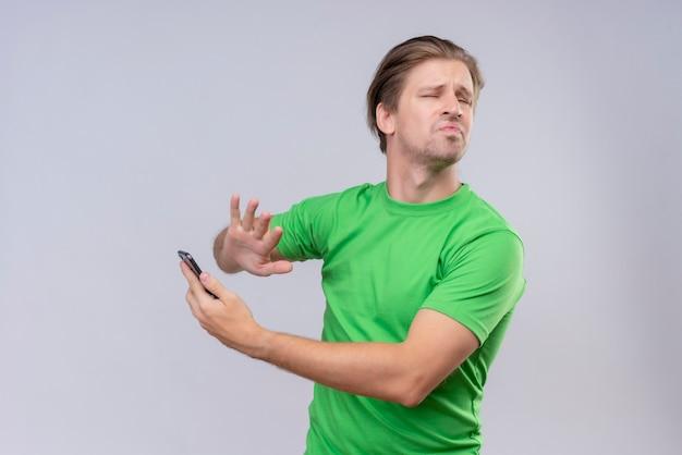 Молодой красавец в зеленой футболке стоит над белой стеной Бесплатные Фотографии