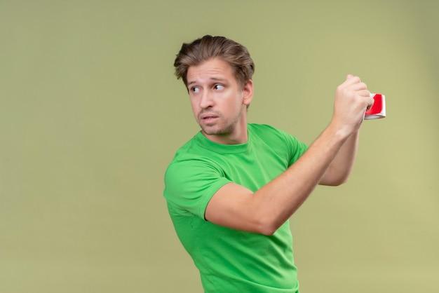 Giovane uomo bello che indossa la maglietta verde utilizzando del nastro adesivo in cerca fiducioso in piedi sopra il muro verde 5 Foto Gratuite